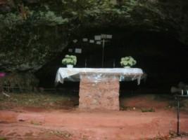 Un autel est érigé dans la grotte de Lourdes.