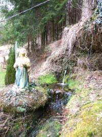 Au pied de la grotte et à proximité de la statue de sainte Bernadette Soubirous, une source claire des Vosges du nord sort de terre.